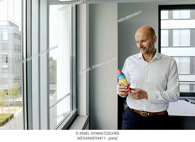Businessman standing by window, holding toy rocket
