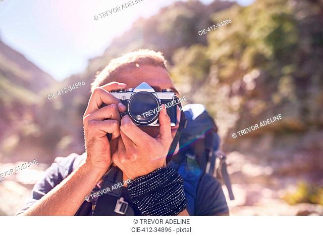 Young man hiking, photographing with camera