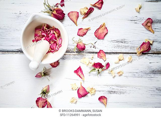 Dried rose petals in a mortar and on a wooden surface
