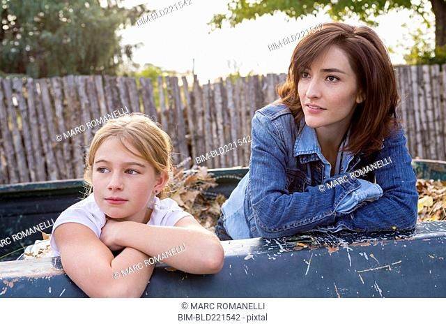 Mother and daughter sitting in truck bed