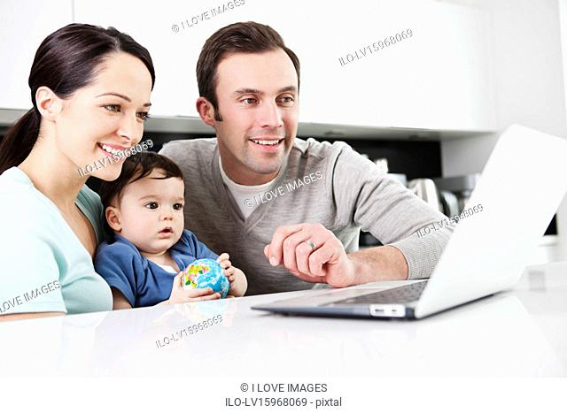 A couple and their baby son looking at a laptop, baby holding a globe ball