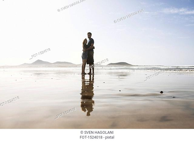 Full length of loving couple embracing at beach on sunny day