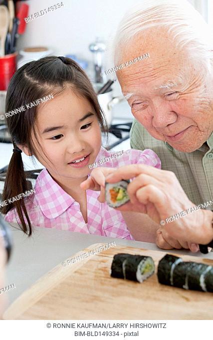 Japanese man teaching granddaughter to make sushi