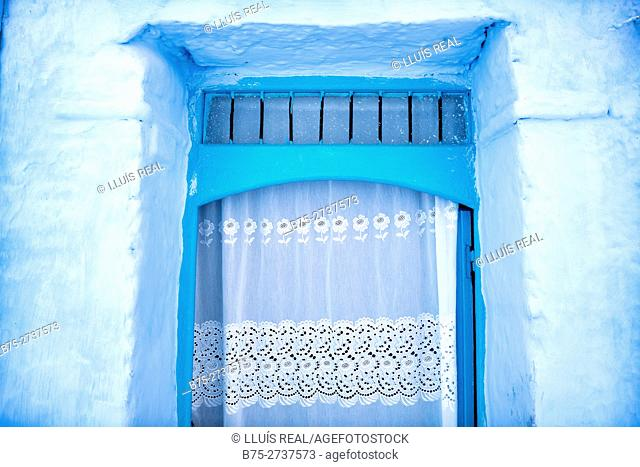 Close-up of a door with a white curtain and blue walls. Chauen, Morocco
