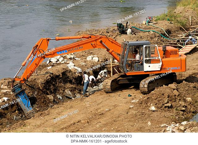 Excavator and digger Bulldozer of TATA HITACHI EX 200 LC heavy machinery ;  excavation work at bank of river Mutha ; Pune ; Maharashtra ; India