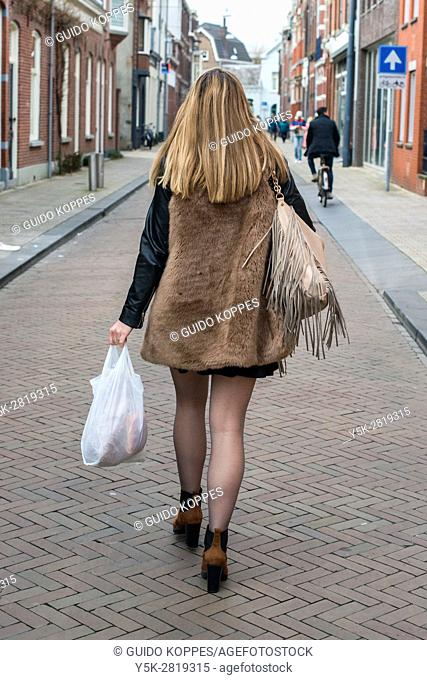 Tilburg, Netherlands. Young, blonde woman walking home through down town streets carrying a shopping bag