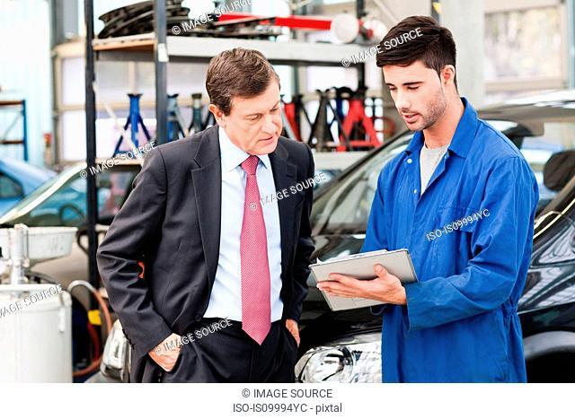 Businessman with car mechanics in repair garage