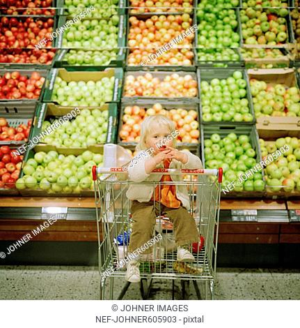 Littel girl sitting in a shopping trolley at the grocery store, Sweden