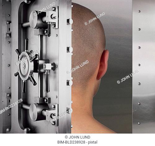 Open vault door revealing shaved-head of man
