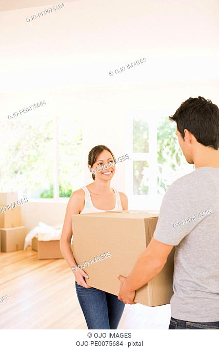 Couple carrying box in their new house