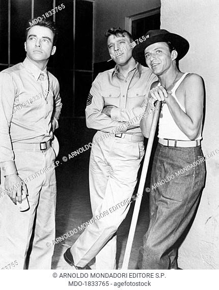 American actors Montgomery Clift, Burt Lancaster who wears a military uniform and Frank Sinatra, who wears a singlet and rests against a cane