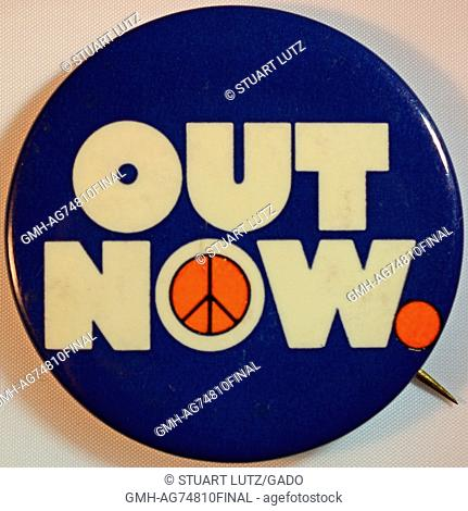 An anti-Vietnam War protest pin that contains the text 'Out now' with a peace sign making up the inner portion of the 'o' in the word 'now', 1968