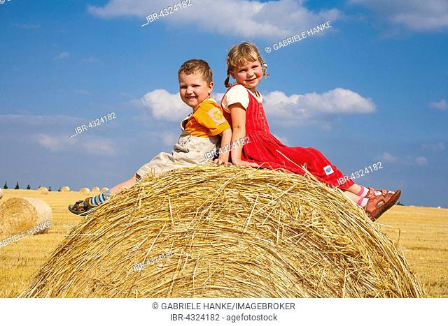 Girl and boy, siblings sitting on a bale of straw in a harvested cornfield, Germany