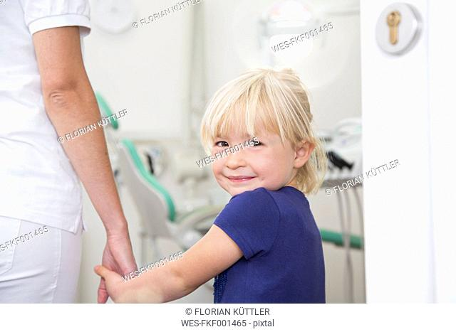 Dental assistant holding girl's hand before treatment
