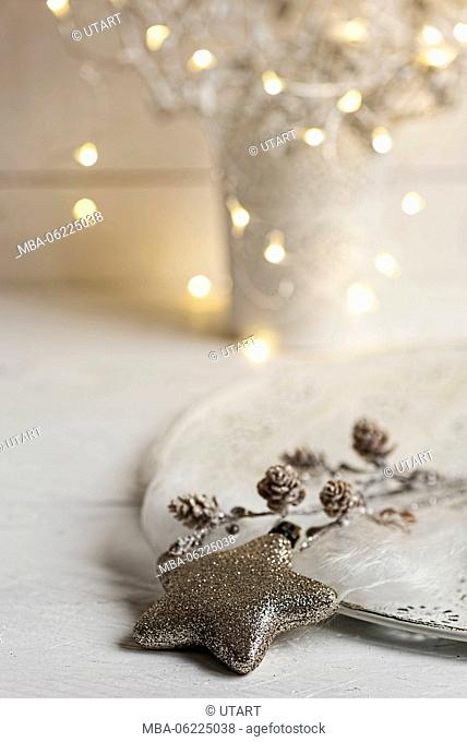 Christmas Still Life with golden glitter star and cones on a white plate, in background Christmas Lights