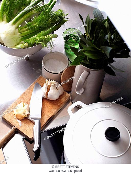 Kitchen counter and hob with chopping board and vegetables