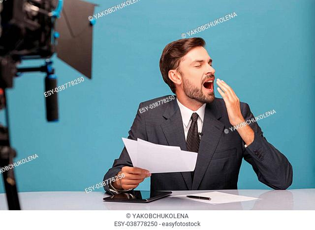 Professional male tv reporter is very tired. He is sitting at desk and yawing with closed eyes. The man is holding documents at studio