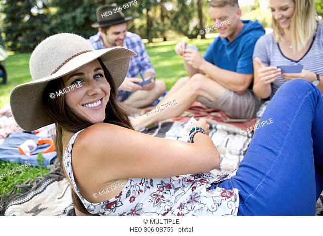 Portrait smiling woman playing cards with friends in summer park