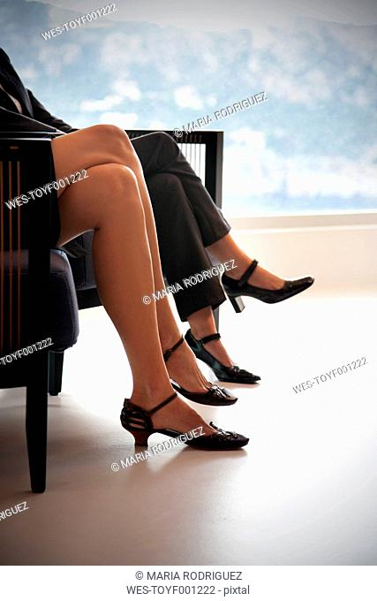 Legs of two businesswomen sitting siede by side on two armchairs