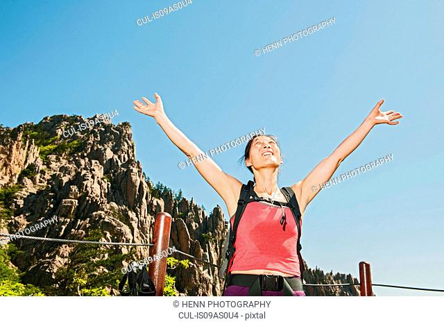 Female hiker with arms raised on way to Daecheongbong peak, Seoraksan National Park in South Korea
