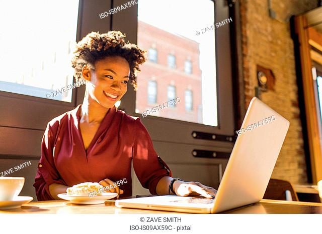 Young businesswoman sitting in cafe, using laptop