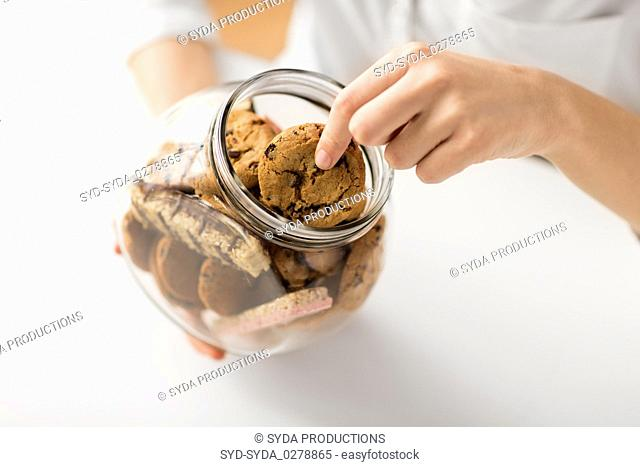 close up of woman taking oatmeal cookies from jar