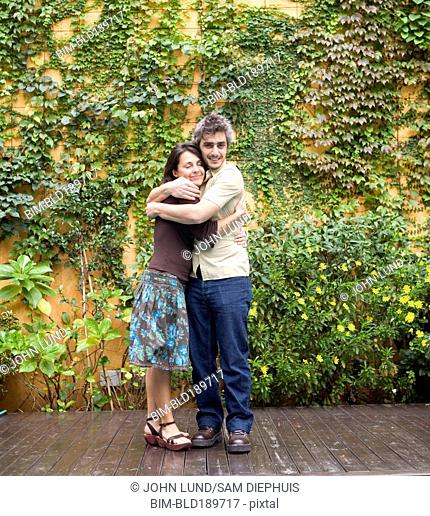 Couple hugging next to plant covered wall outdoors
