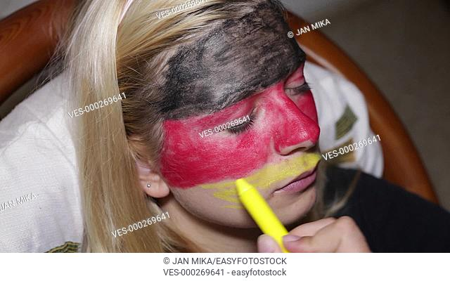 Closeup of a woman face painting flag of Germany