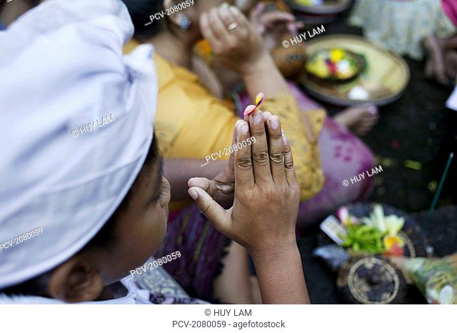 Close up of hands in prayer position during Kuningan Festival; Bali, Indonesia