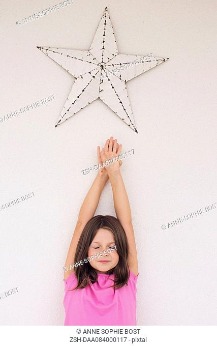 Girl reaching toward star shape hanging above her head, eyes closed