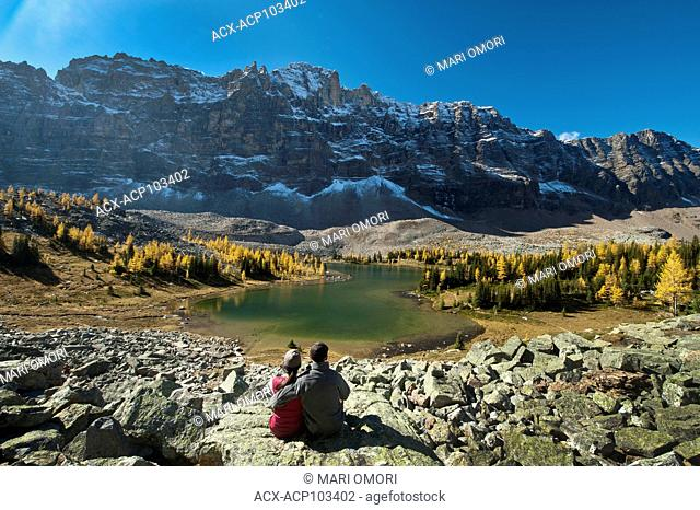 A couple takes a break to view the golden Larches that grow along the trails in Yoho National Park. Model Release signed