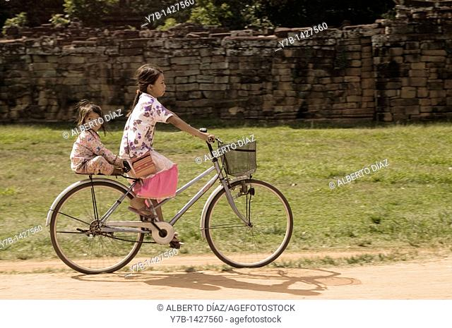 Girls riding bikes through the temples of Angkor Wat