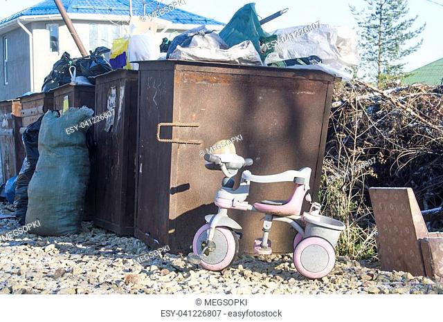 tricycle, discarded to cesspool. concept of a bygone childhood