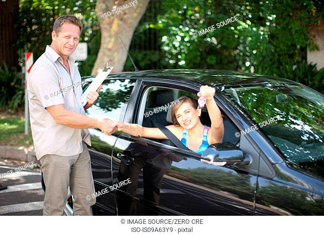 Driving instructor congratulating student