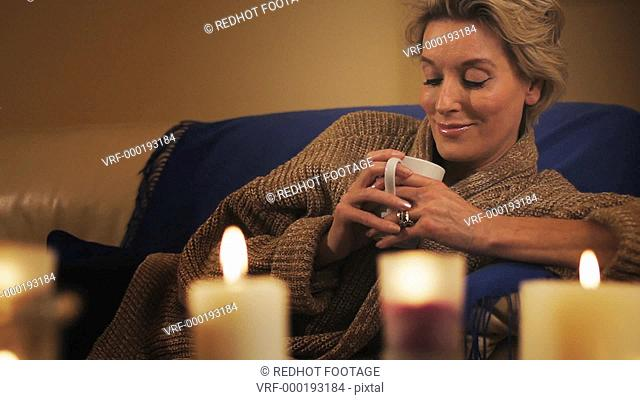 Dolly shot of woman lying on sofa with in the evening with beverage