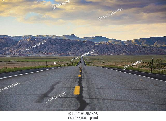 Road leading towards rocky mountains against cloudy sky