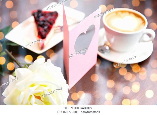 holidays, valentines day and love concept - close up of greeting card with heart, flower, cake and coffee over holidays lights