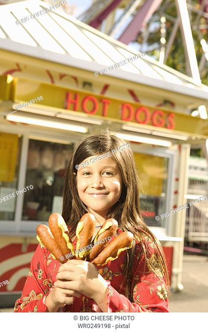 Young teen girl holding corndogs