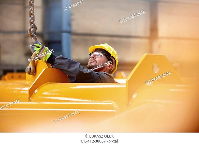 Male worker attaching chain to equipment in factory