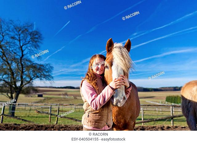 Loving portrait of a happy girl and her horse outdoors on a bright sunny day