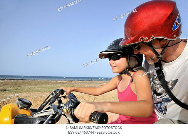 Girl (10) driving an ATV with her dad by seacoast, Djerba Island, Tunisia