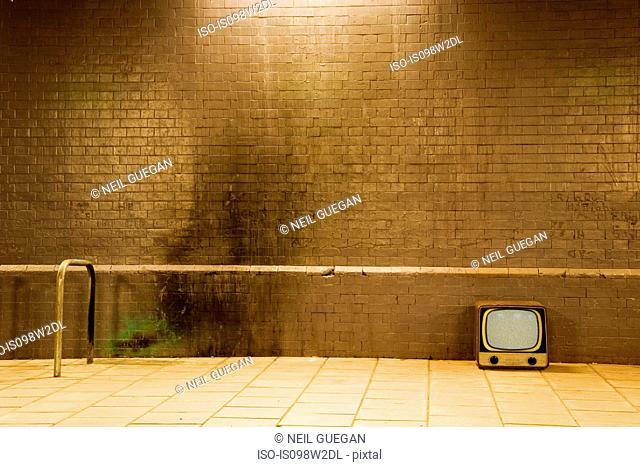 Retro television by brick wall
