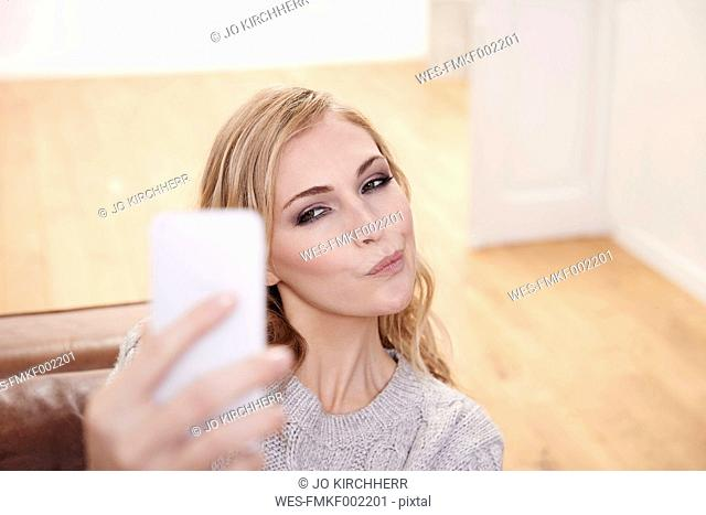 Young woman pouting mouth taking selfie