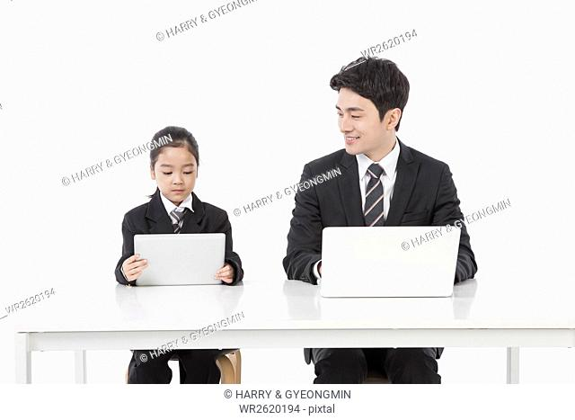 Businessman and his daughter using notebook computer
