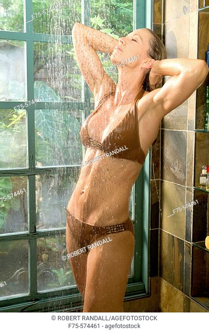 Young woman in brown bathing suit rinses off in shower
