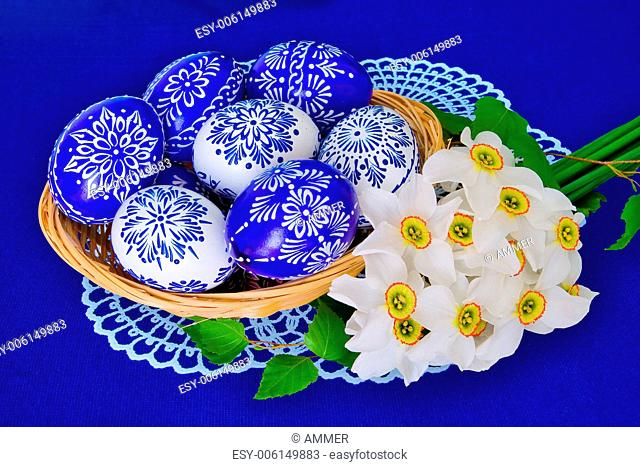 Blue and white ornamental Easter eggs and bouquet of daffodils