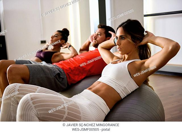 Young people doing crunches on a gym ball