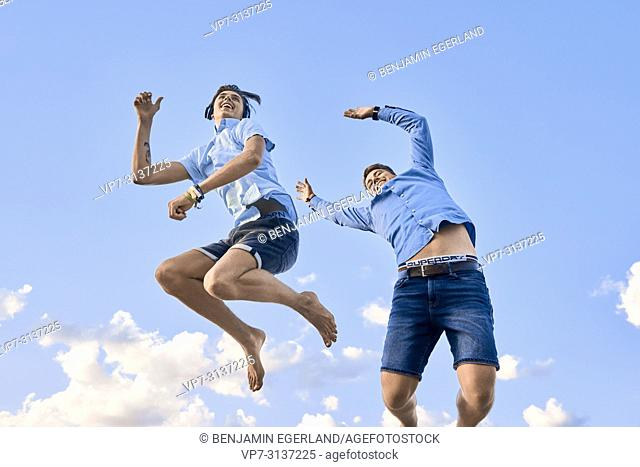 Two friends jumping against sky, young men, students, energetic, vibrant, lively, adventure, teenage, adolescence, best friends, togetherness, enjoying life