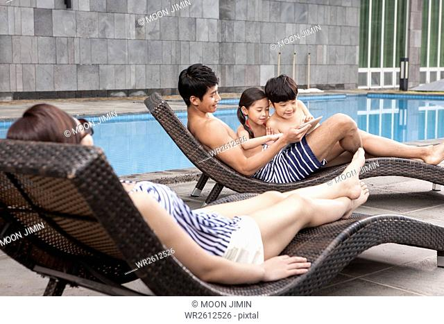 Harmonious family having summer vacation at outdoor swimming pool