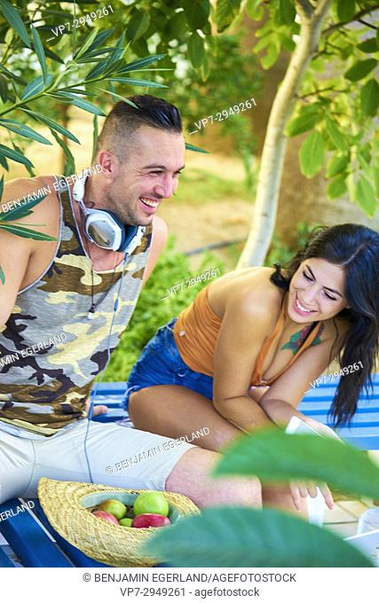 young couple laughing together in nature. With headphones and healthy apples. Greek ethnicity. In late summer / September